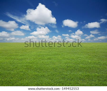 Green lawn with blue sky with clouds - stock photo