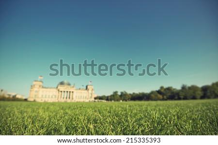 green lawn with the blurred Reichstag building in background, the national german parliament, Berlin, Germany, vintage style gr�¼ne Wiese mit dem Reichstagsgeb�¤ude, Sitz des deutschen Bundestages - stock photo