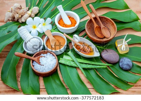 Green leaves with nature spa ingredient turmeric powder in white mortar ,ginger,herbal compress ball,honey,soap,cinnamon powder ,wooden bowl ,wooden spoon and sea salt. - stock photo