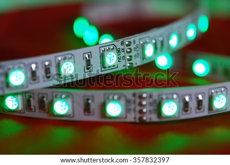 Green led strip on the background of red textile - stock photo