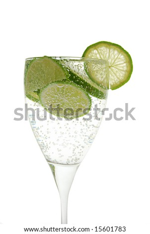 Green lemon in the glass with water. On the white background - stock photo