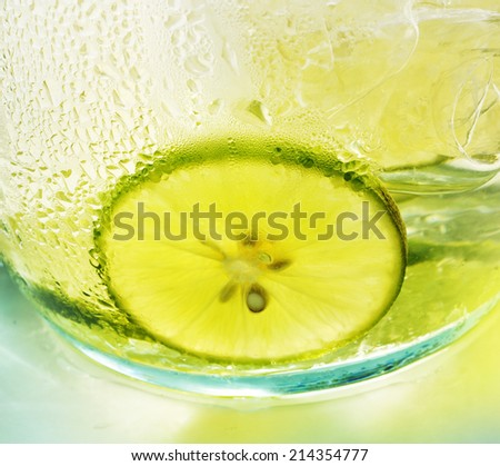 Green lemon with ice tea - bright colors - stock photo