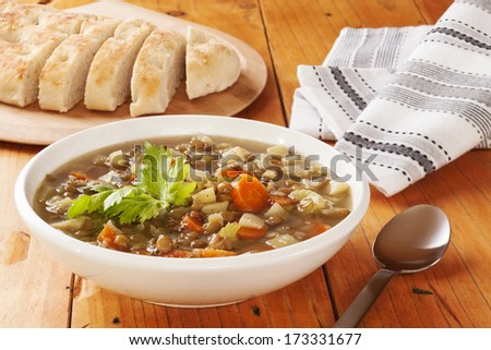 Green Lentil Soup - a bowl of green lentil soup with bread. - stock photo