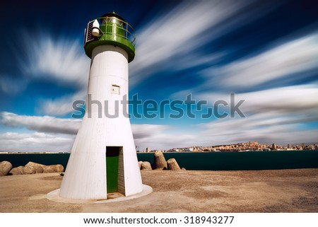 Green lighthouse in the enter of the Harbor with long exposure to move the clouds - stock photo