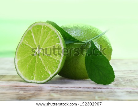 Green limes with leaves on wooden background - stock photo