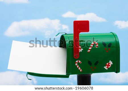 Green mailbox with blank card and the flag up on a blue sky background, mailbox - stock photo