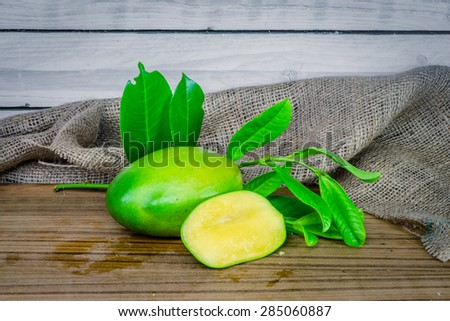 Green mango on a wooden table - stock photo