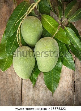 Green mango on wood background - stock photo
