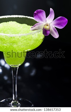 Green margarita cocktail in front of disco lights - stock photo