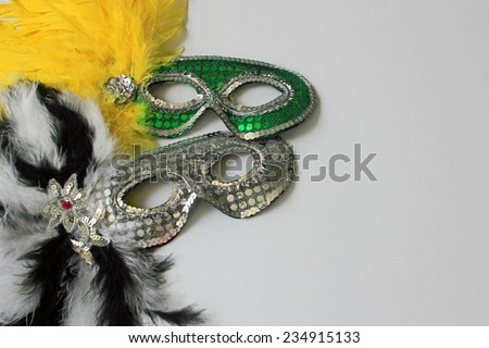 Green mask with yellow feathers and silver mask with black and white feathers symbolizing New Year's Eve parties, celebrations and disguise with white copy space on the right hand side - stock photo
