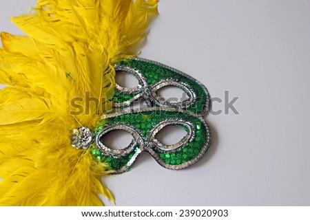 Green masks with yellow feathers symbolizing New Year's Eve parties, celebrations and disguise with white copy space on the right hand side - stock photo