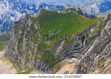 Green meadow above geological layers visible on the mountain side - stock photo