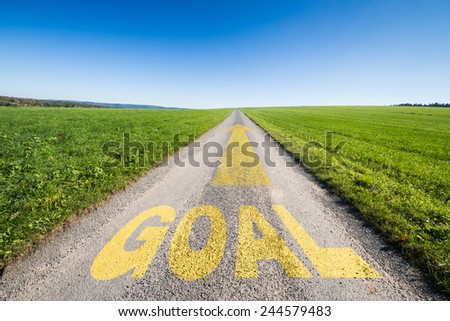 green meadow and a small tar road with an yellow arrow  leading  to the horizon. On the road is written the word goal. Concept for business growth and success.  - stock photo