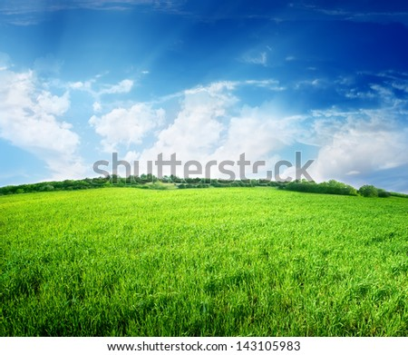 Green meadow and blue sky lit by the sun - stock photo
