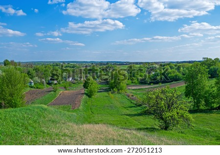 Green meadow and trees on the outskirts of countryside in early spring - stock photo
