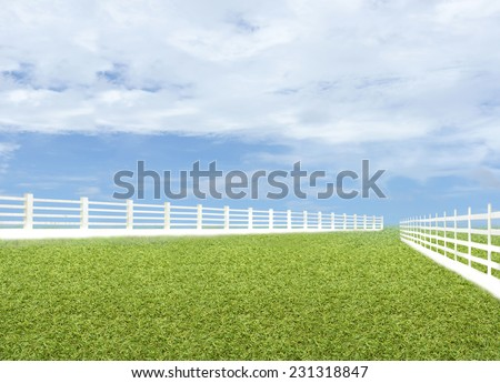 Green meadow blue sky with white fence - stock photo
