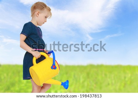green meadow, cute charming girl pours from a yellow watering can, now grass will grow tall and juicy. - stock photo