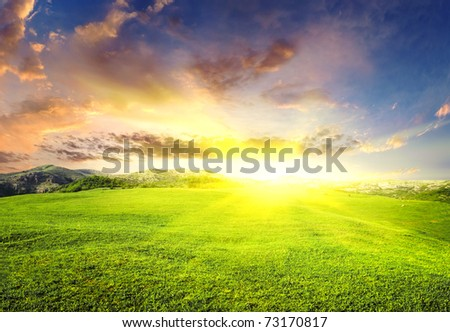 Green meadow during sundown with bright sun - stock photo