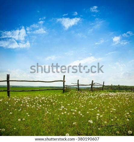 Green meadow under blue sky with clouds. Village landscape - stock photo