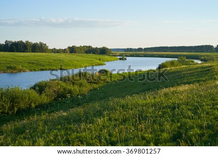 Green meadow with lake and hills - stock photo