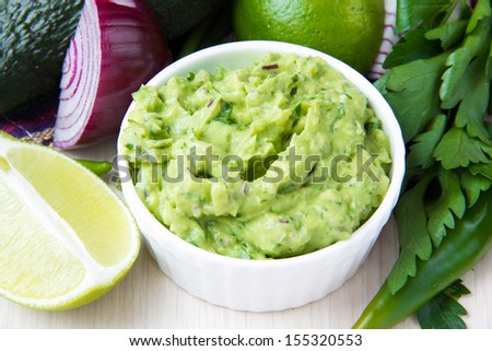 Green Mexican guacamole dip with avocado, lime, parsley and red onions in white ���up and vegetables around - stock photo