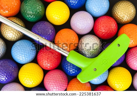 Green mini golf putter with balls of assorted colors - stock photo