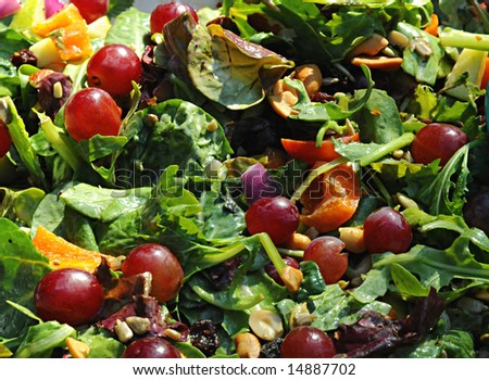 Green mixed salad full of nuts and fruit - stock photo