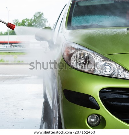 Green modern automobile in the car wash - stock photo