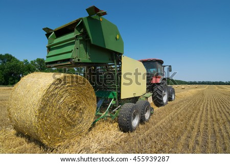 Green modern tractor makes big straw roll on yellow field at summer day - stock photo