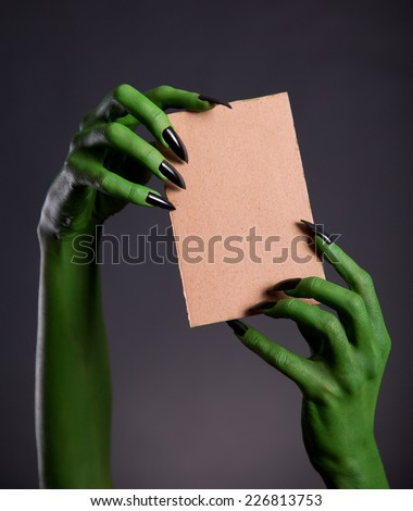 Green monster hands holding empty piece of cardboard, Halloween theme   - stock photo