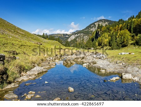 Green mountain forest landscape with river and trees, green grass hills, blue sky, Switzerland - stock photo