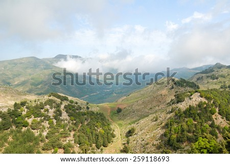 Green mountains and white clouds on the island of Crete, Greece - stock photo