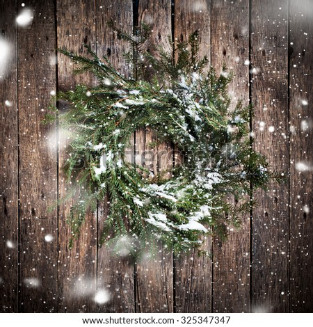 Green Natural Wreath on Wooden Background with drawing Falling Snow. Vintage Style - stock photo
