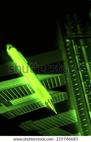 Green neon image of pen and ruler on blueprints of building - stock photo