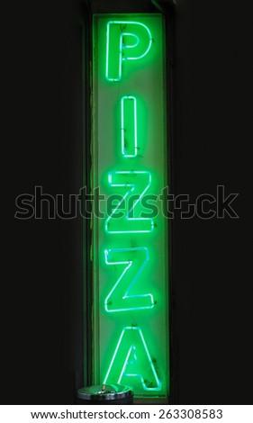 Green neon light pizza sign marking a pizzeria restaurant - stock photo