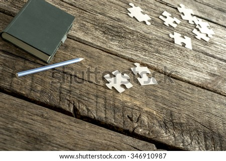 Green note pad, pencil and scattered puzzle pieces lying on a textured wooden desk. Conceptual of education, research and problem solving. - stock photo