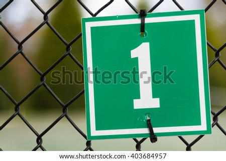 Green Number One Sign on Chain Link Fence - stock photo