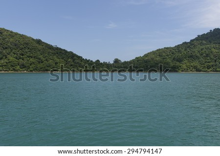 green ocean and blue skies with mountains in the background - stock photo