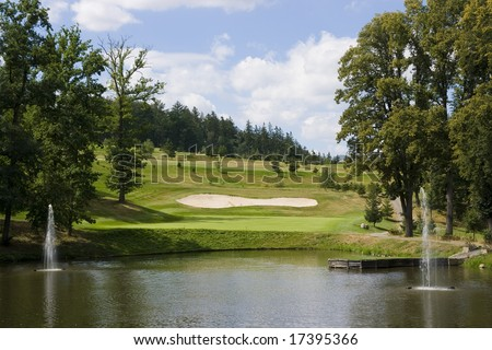 green of a beautiful golf course behind lake with dramatic summer sky - stock photo
