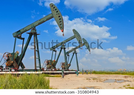 Green Oil pump oil rig energy industrial machine for petroleum crude on the side of dirt road - stock photo