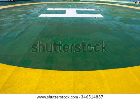 Green oil rig helipad with yellow circle line - stock photo