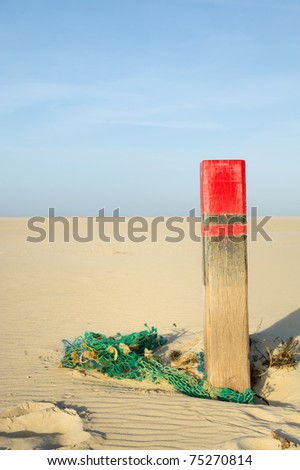 Green old fishing net and wooden pole at the beach - stock photo