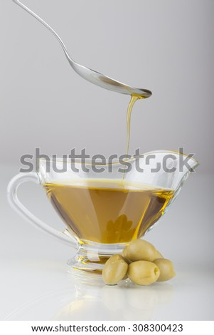 green olives and oil on white background - stock photo