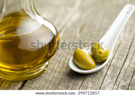 green olives and olive oil on old table - stock photo