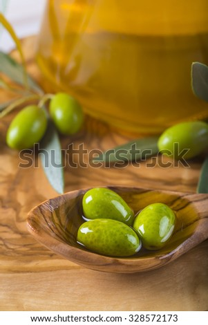 Green olives and virgin olive oil on a wooden spoon - stock photo