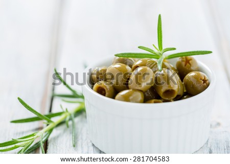 Green olives in a small white bowl on a rustic wooden table with rosemary - stock photo