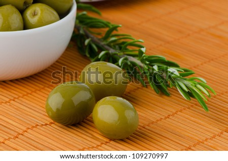 Green olives in a white ceramic bowl and oil decanter set. - stock photo
