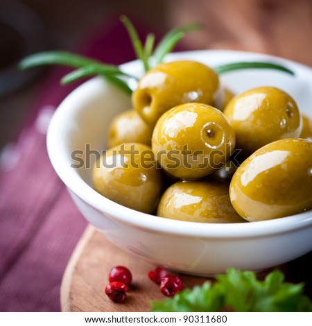 Green olives in a white dish - stock photo