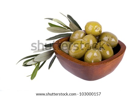Green olives in a wooden bowl with olive branch. Isolated on white - stock photo