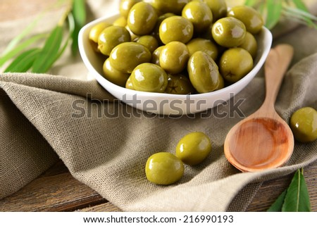 Green olives in bowl with leaves on table close-up - stock photo